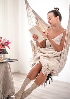 ハンモックの椅子に本を持っている美しい若い女性。休息と家庭の快適さの概念。