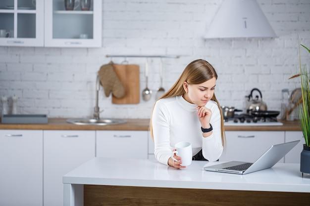 Красивая молодая женщина со светлыми волосами в белом свитере с высоким воротом стоит на белой кухне и работает за ноутбуком, она пьет кофе. работайте удаленно из дома