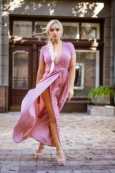 Красивая молодая женщина со светлыми волосами в розовом платье идет по улице города