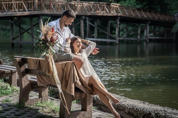 꽃을 든 아름다운 젊은 여성과 남편이 벤치에 앉아 의사소통, 자연에서의 데이트, 결혼의 로맨스를 즐기고 있습니다.