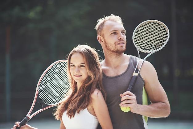 夫と一緒に美しい若い女性が屋外テニスコートを着用します。 Premium写真