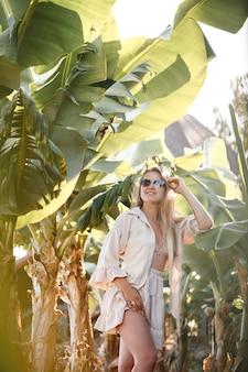 유럽풍의 긴 금발 머리를 한 아름다운 젊은 여성이 바나나 나무 근처에 서 있습니다. 화창한 여름 날에 열 대 숲에서 소녀입니다. 선택적 초점