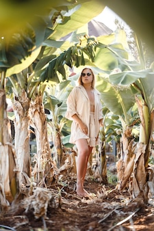유럽풍의 긴 금발 머리를 한 아름다운 젊은 여성이 바나나 나무 근처에 서 있습니다. 화창한 여름날 열 대 숲에 있는 소녀