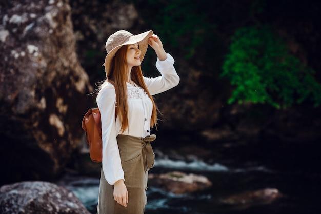 森の中の騒々しい川の近くで帽子とバックパックを身に着けている赤い髪の美しい若い女性。