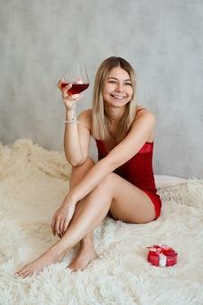 Красивая молодая женщина с улыбкой сидит в красном нижнем белье на белом пледе с вином в руке. утро дня святого валентина. вертикальное фото