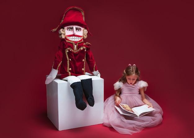 くるみ割り人形の近くに座って、赤いスタジオで本を読んでいる美容バレリーナ
