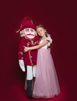 Красавица балерина, которая держит щелкунчик в красной студии