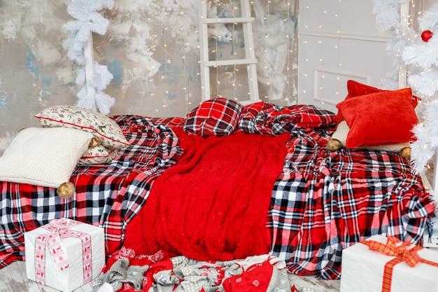 새해 장식, 빨간 침대보와 노란 화환이 있는 침대. 크리스마스에 집을 꾸미기