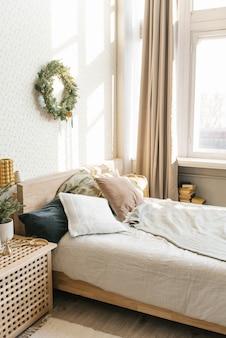 스칸디나비아 스타일의 침실에 베개와 크리스마스 장식이 있는 침대