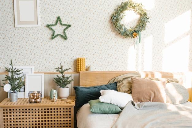 Кровать с подушками и елочными украшениями в спальне в скандинавском стиле.