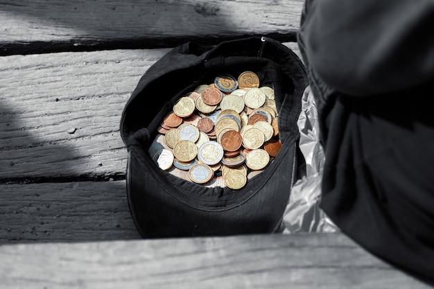 한 거지가 동전이 든 모자 옆에 앉아서 자선을 청합니다. 약간의 자선 동전이 있는 모자
