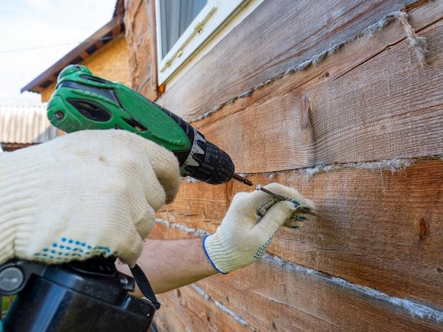 Новичок пытается при помощи электрической отвертки вбить гвоздь в стену. ошибки в использовании инструментов. выборочный фокус