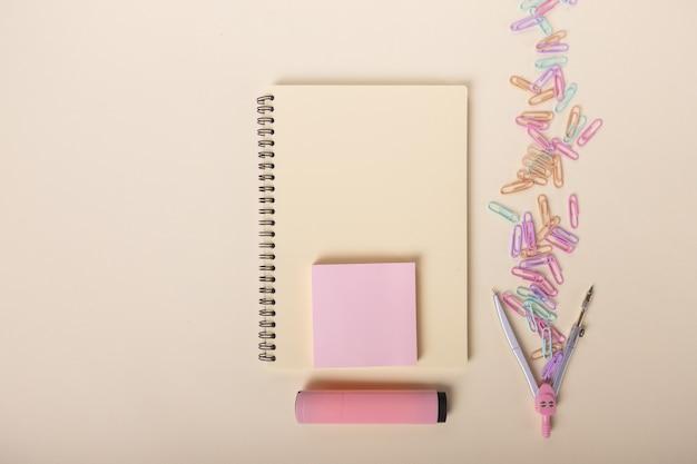 Бежевая тетрадь розовым маркером компас и цветные скрепки красиво разложены на светлом ...