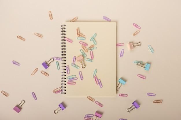 베이지색 노트북 및 베이지색 배경 교육 용품 b에 많은 색 흩어져 있는 종이 클립...