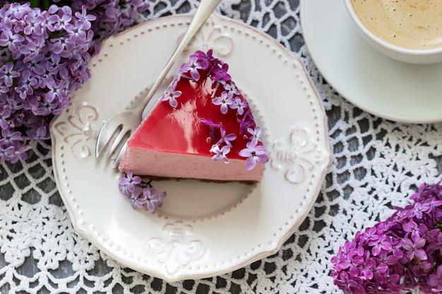 ライラックの花で飾られたチョコレートベースとジュースゼリーのベリーのムースケーキとコーヒー。