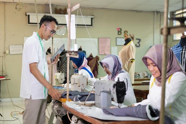 Азиатский мужчина в очках с рулеткой на шее и планшетным пк