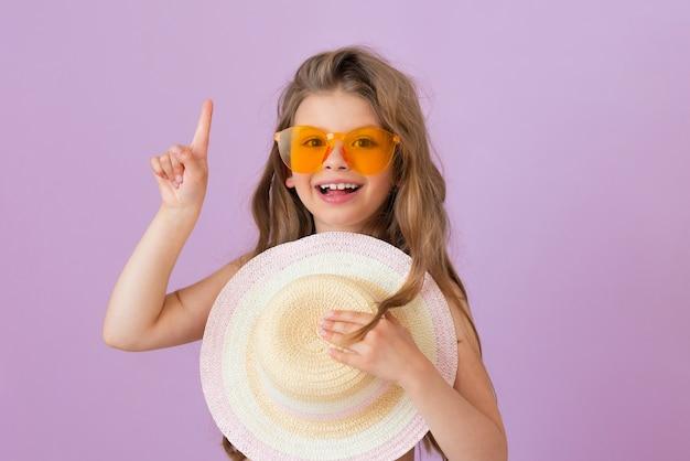 안경을 쓴 아기가 광고를 가리키며 밀짚모자를 쥐고 있습니다.
