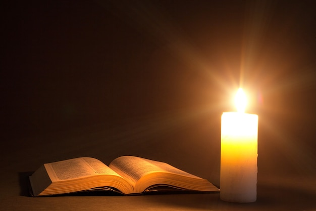 Библия на столе при свете свечи