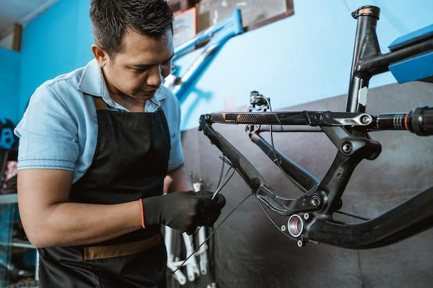 자전거 정비사가 자전거 프레임을 조립하면서 브레이크 케이블을 연결합니다.