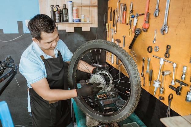앞치마를 입은 자전거 정비사가 자전거 바퀴를 수리하는 동안 프리휠을 확인합니다