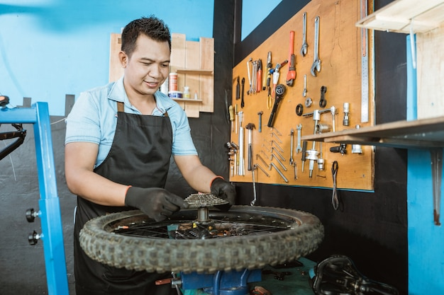 장갑을 끼고 앞치마를 입은 자전거 정비사가 프리휠을 설치합니다.