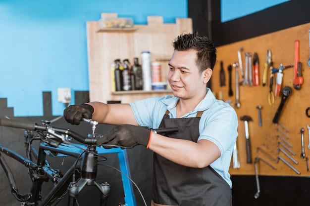 쇼크 렌치를 사용하여 장갑을 끼고 앞치마를 입은 자전거 정비사