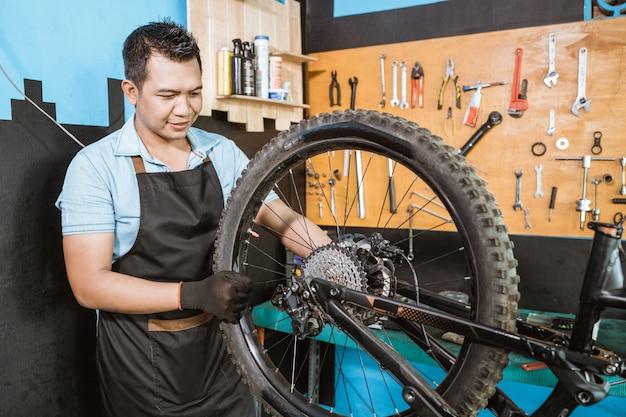 앞치마를 입은 자전거 정비사가 자전거 프레임을 조립할 때 장갑을 끼고 바퀴를 설치합니다.