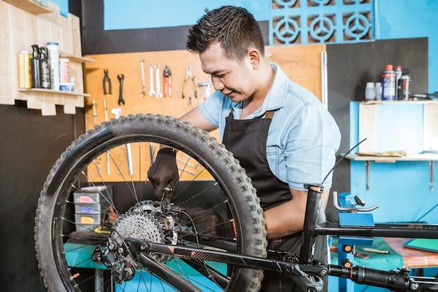 エプロンの自転車整備士は、自転車を修理するときに自転車のブレーキをかけます