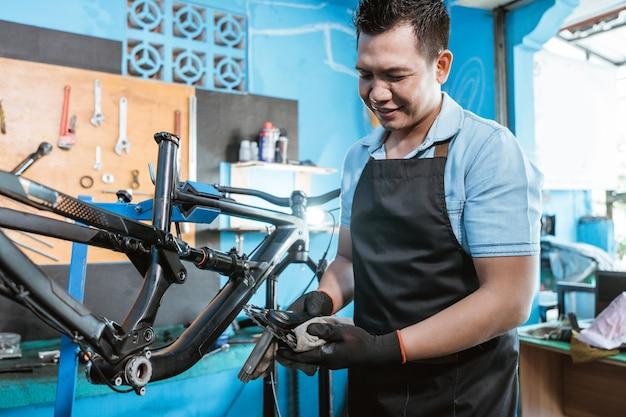 앞치마를 입은 자전거 정비사가 크랭크 세트를 새 자전거에 설치하는 동안 잡고 있다