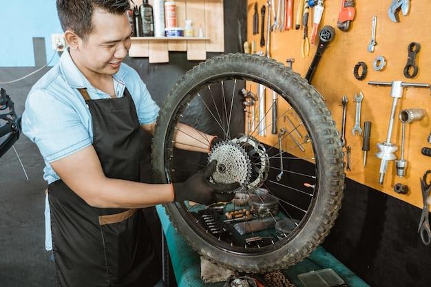 앞치마를 입은 자전거 정비사가 자전거 바퀴에 프리휠을 설치하는 동안 프리휠을 잡고 있습니다.