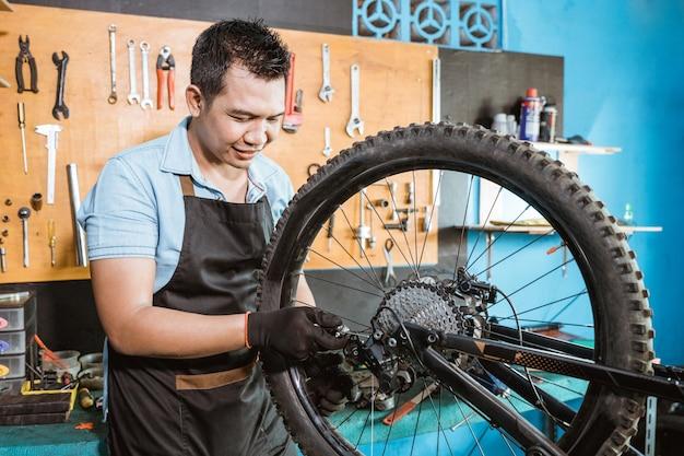 앞치마를 입은 자전거 정비사가 문제를 해결하는 동안 후방 기계를 잡고 있습니다.