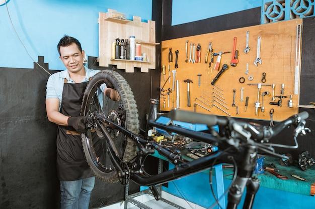 앞치마를 입은 자전거 정비사가 자전거 프레임을 조립할 때 바퀴를 설치합니다.