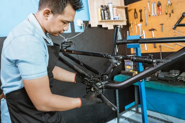 자전거 정비사가 조립하면서 자전거 크랭크 세트를 설치합니다.