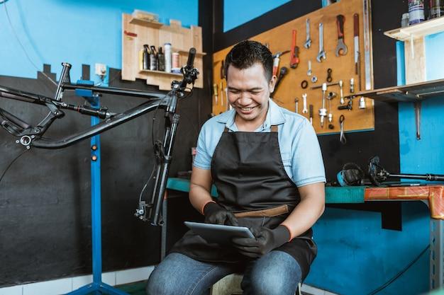 자전거 정비사가 디지털 태블릿을 사용하여 앉아 있습니다.