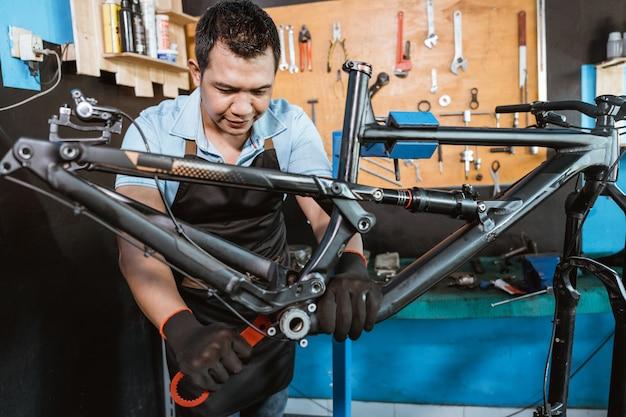 자전거 정비사가 바텀 브래킷 렌치를 사용합니다.