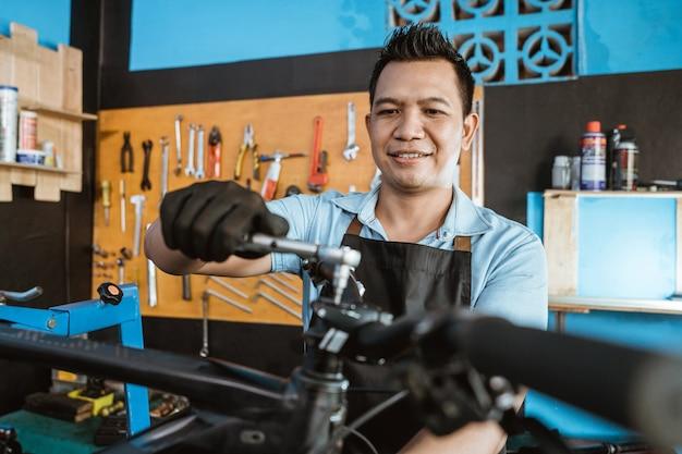 자전거 정비사가 도구를 사용하여 핸들바 볼트를 풉니다.