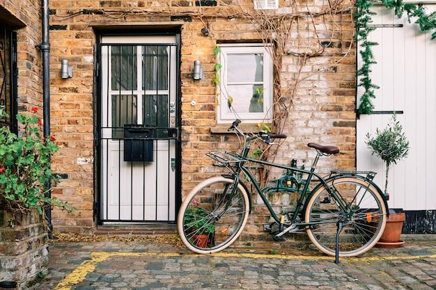 낮에 식물로 장식 된 벽돌 건물 근처에 주차 된 자전거