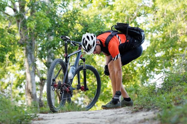 Велосипедист с горным велосипедом в лесу затягивает застежку велосипедной обуви.