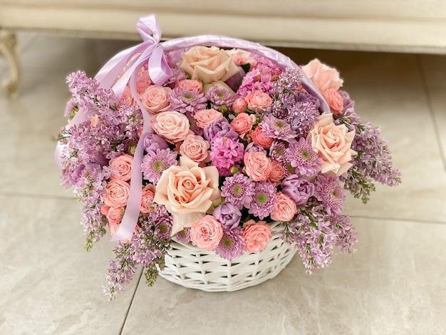 Большая красивая корзина с нежными розовыми цветами. хризантемы, розы, сирень, тюльпаны, гиацинты. романтический подарок к празднику. фоновое изображение цветочного магазина