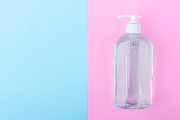 Большая бутылка с антисептическим дезинфицирующим гелем для мытья рук на синем и розовом фоне. алкоголь гель как профилактика коронавируса. концепция профилактики вирусных заболеваний.