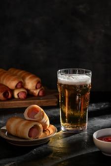 ケチャップと生地の軽いビールとソーセージの大きなガラス