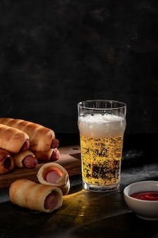 ソースと生地の軽いビールとソーセージの大きなガラス