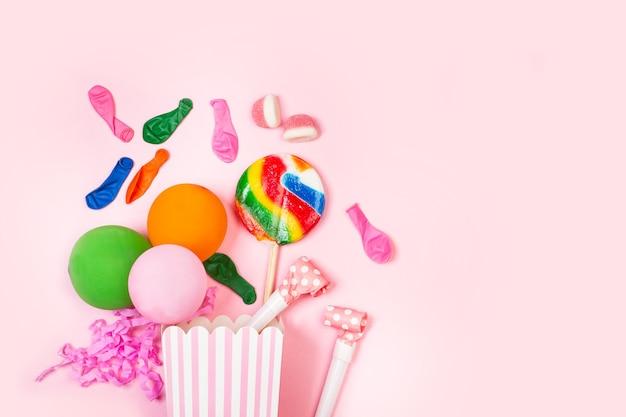 복사 공간이 분홍색 배경에 파티 것들과 큰 여러 가지 빛깔의 롤리팝