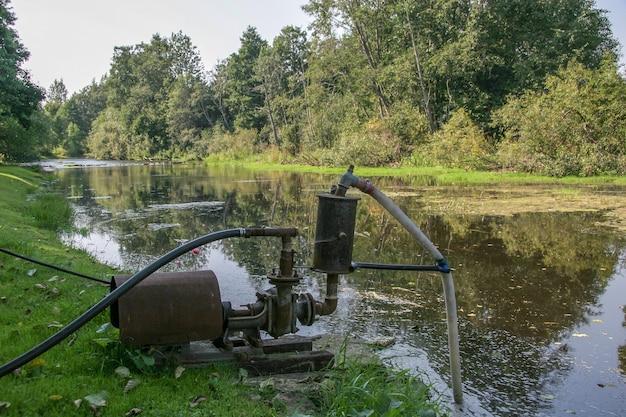 Большой старый водяной насос стоит на берегу реки и качает воду. река заросла травой. на берегу растут деревья.