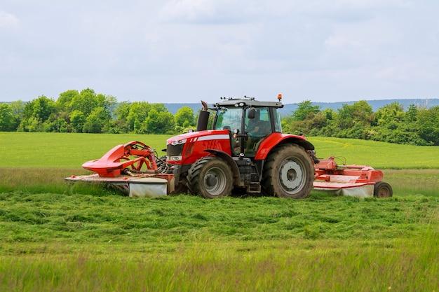 두 개의 모어가 달린 큰 빨간 트랙터는 사일로에서 푸른 잔디를 깎습니다.