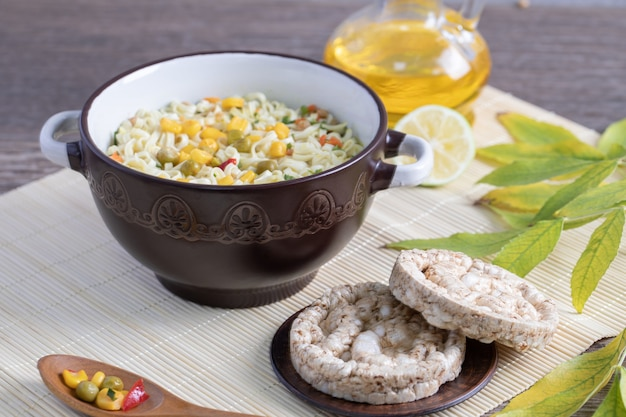 Большая кастрюля вкусной лапши с кукурузой, горошком и круглыми хлебными корками