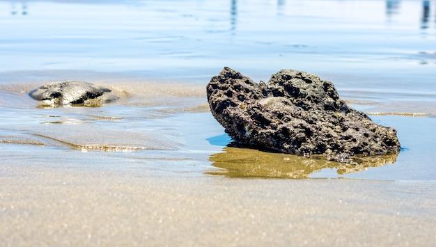 모래 해변에 있는 큰 돌은 반사가 있는 전망을 닫습니다.