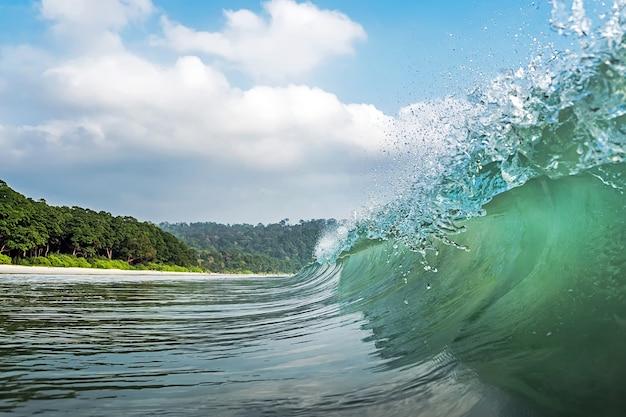 큰 파도가 덮고 있습니다. 인도 안다만과 니코바르 섬의 라다나가르 해변. 바다에서 볼 수 있습니다. 바다에서 물의 파열입니다. 물방울의 스프레이. 파도의 마루 아래. 파도의 문장