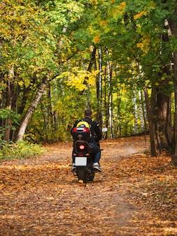 Байкер на мотоцикле едет по лесной дороге с рюкзаком за спиной. пикник на природе.