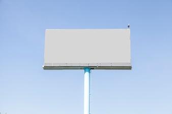 A bird perching on gray empty billboard against blue sky